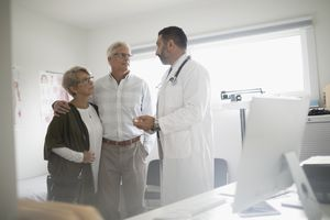Male doctor talking with senior couple patient in doctor