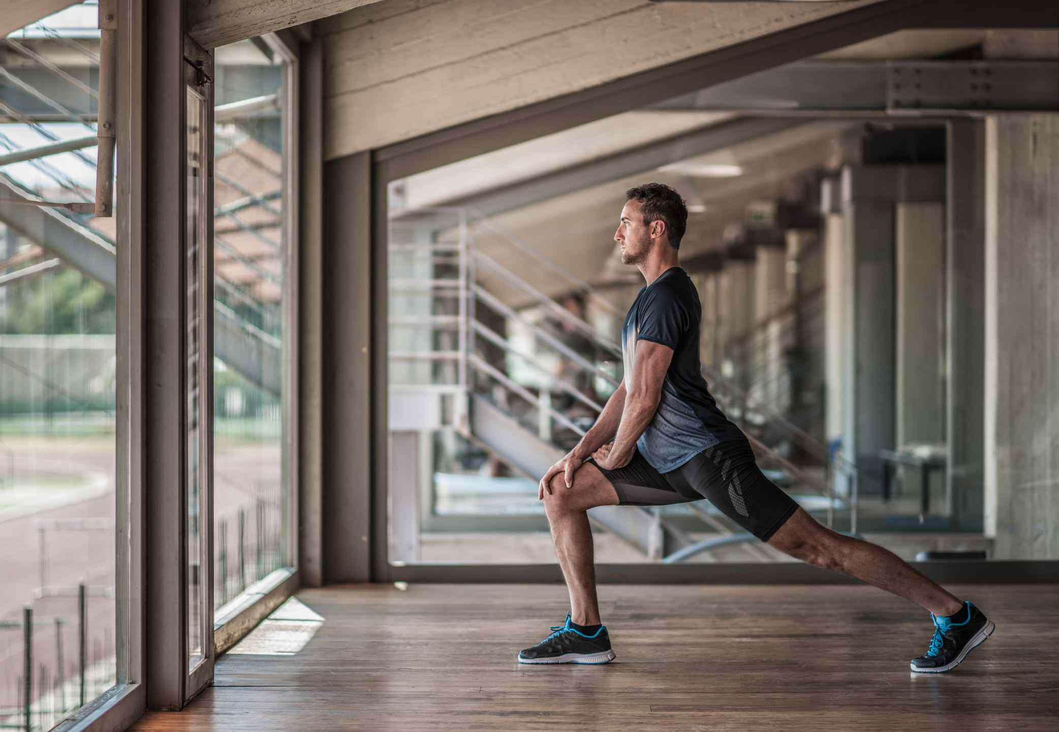 Man doing a leg lunge in a sports stadium