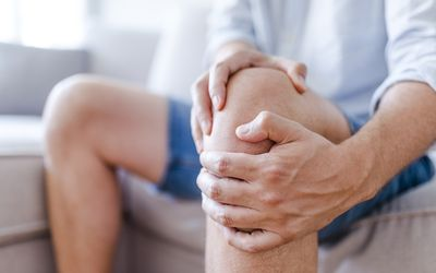 A mature man massaging his painful knee