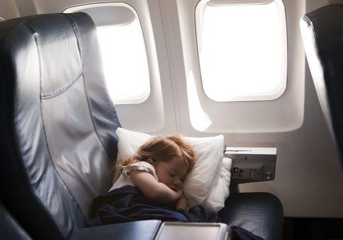Little girl sleeping in airplane seat.