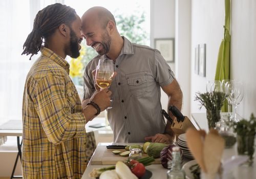 Two men with wine in a kitchen prepping dinner