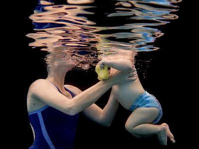 Woman holding a toddler in swimming pool