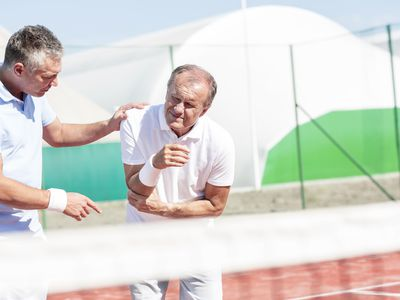 Man assisting tennis player with pain