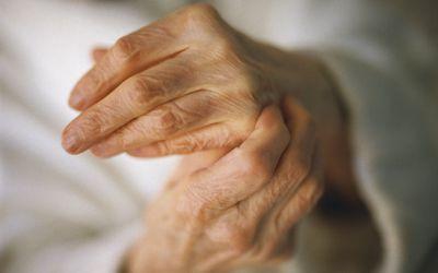 An older woman rubbing her sore hands