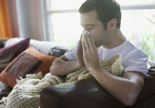 Allergies and vitamin D deficiency. Man blowing nose at home on couch