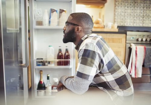 Hungry man looking for food in the refrigerator
