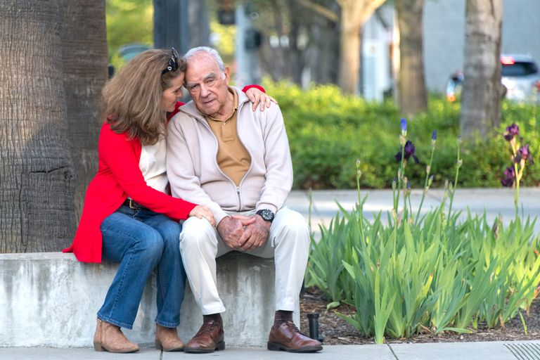 An older man sits outside with his wife holding him