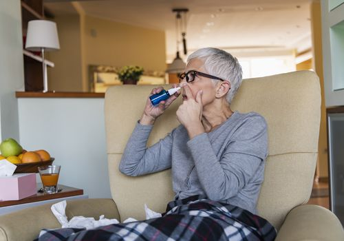 Older woman using nasal spray