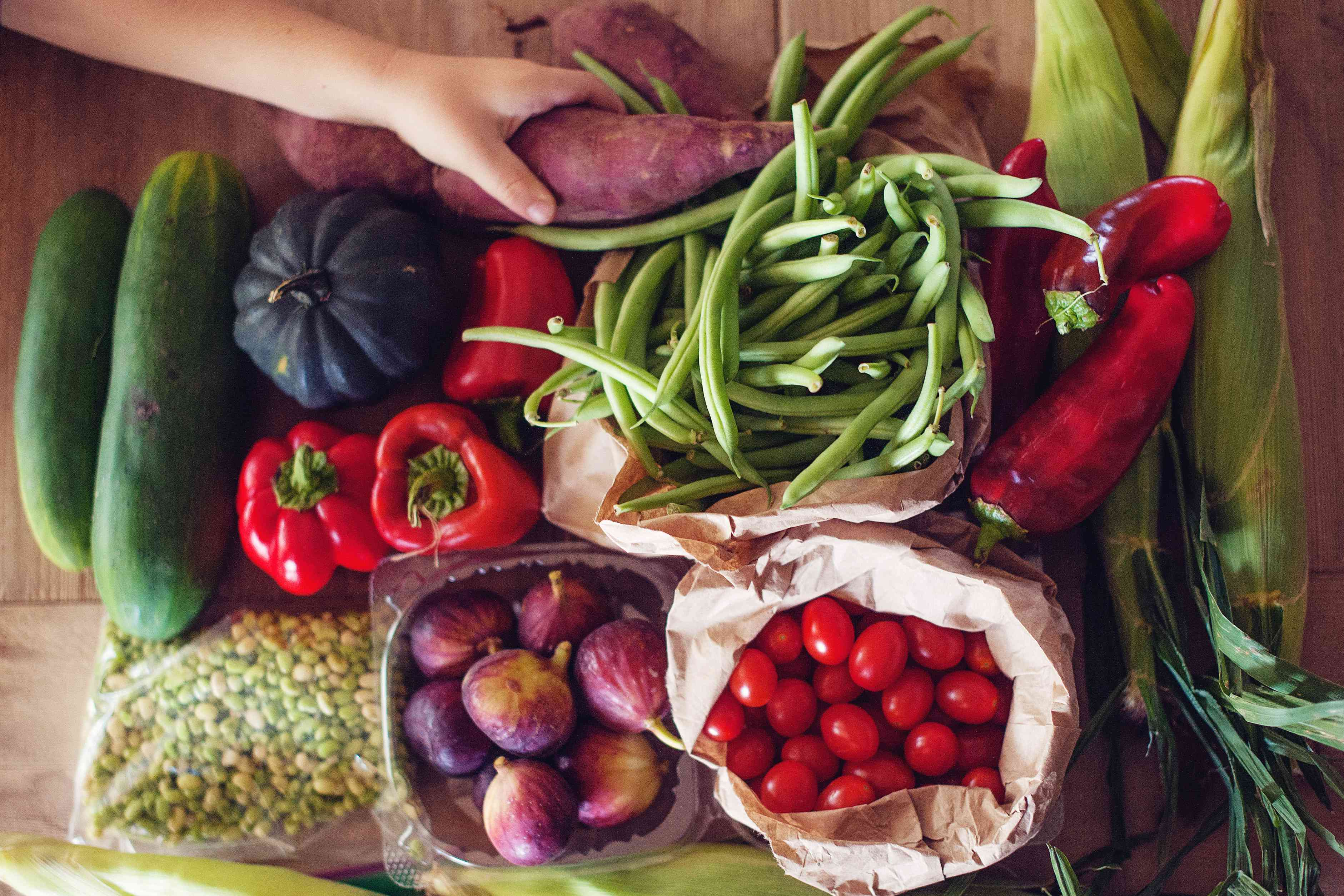 Close-up of hand reaching for fresh vegetables on wooden table