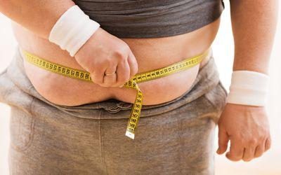 Closeup of man measuring his waist circumference