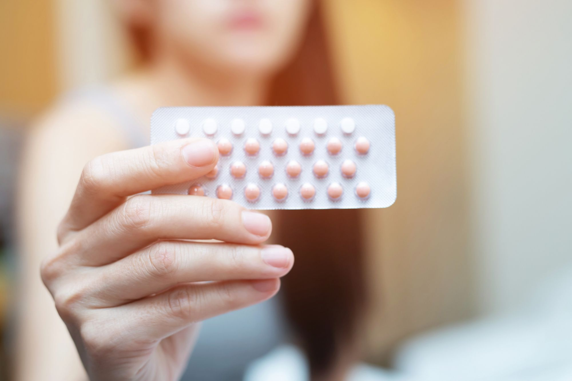 Woman holding up birth control