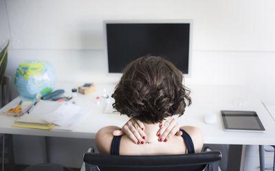 woman rubbing sore neck at computer