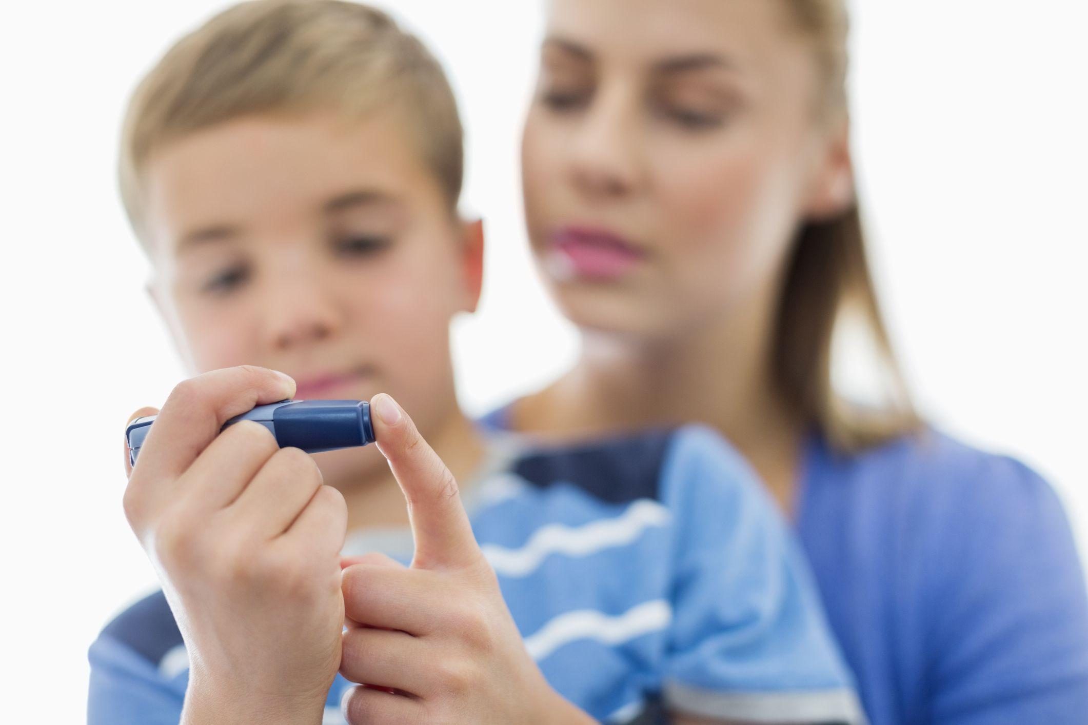 Mom helping son test blood sugar