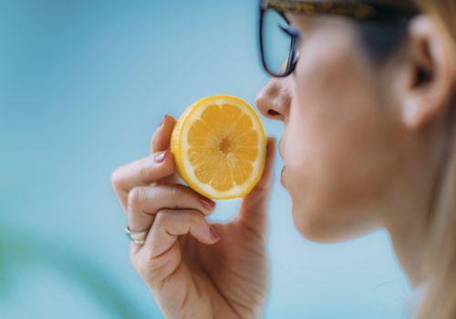 Woman smelling a sliced orange.