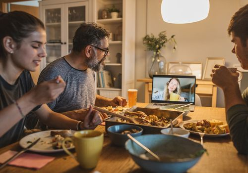 Family at a table with woman dialing in on laptop