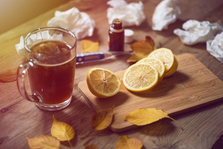 a cup of tea next to a cutting board with sliced lemons