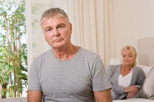Worried couple in bedroom - stock photo