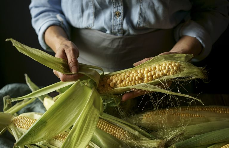 a person shucking corn