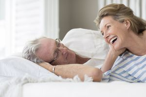 Older couple relaxing on bed
