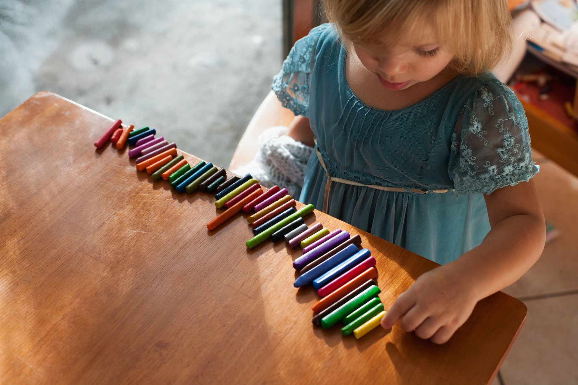 A child lining up crayons