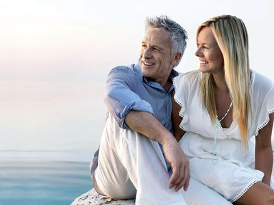 Older man and woman sitting on a rock by the ocean