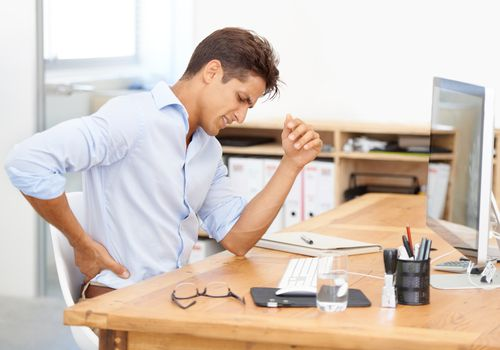 man holding his lower back in pain at a desk