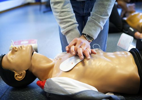 Student practicing CPR in a class on a dummy