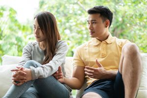 Disappointed Couple Looking Away While Sitting On Sofa