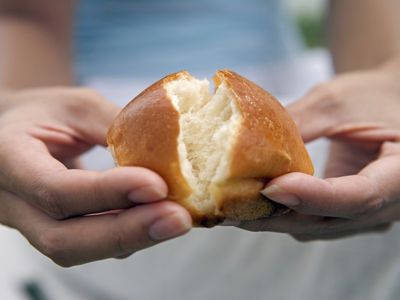 close-up shot of woman breaking bread in her hands