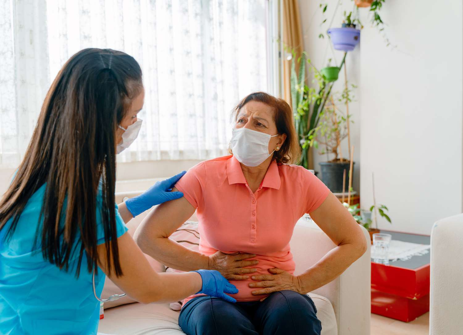 Abdominal pain patient woman having medical exam with doctor - stock photo