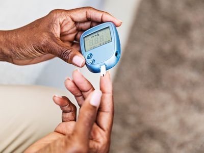 Person using blood sugar meter to check glucose levels