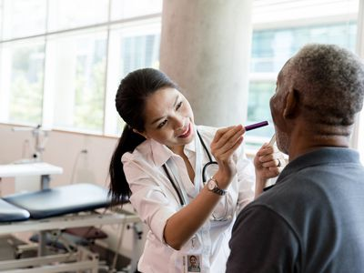 Woman looking at patient's tongue in medical setting
