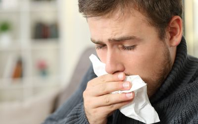 A white man coughing into a tissue.
