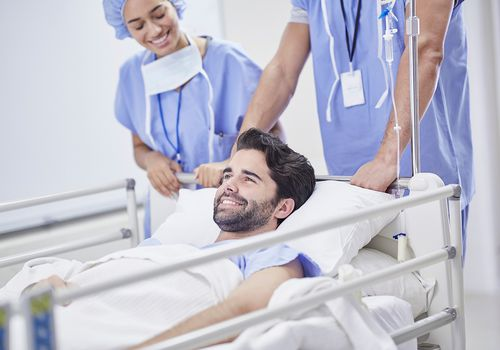 Doctors pushing smiling patient in hospital bed.