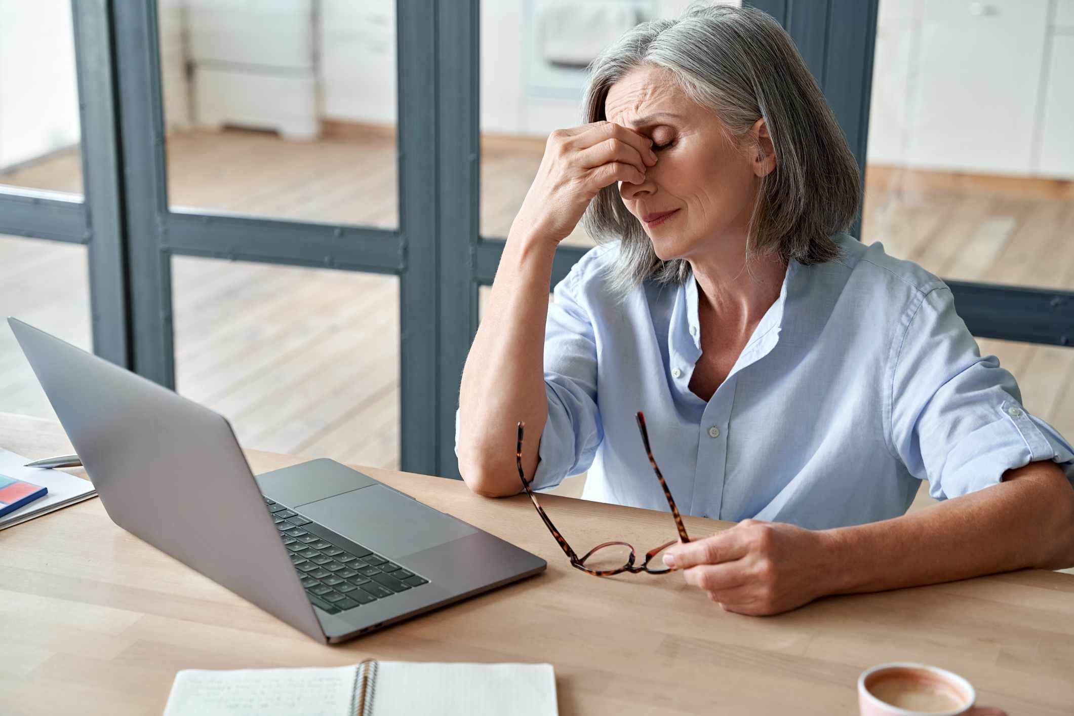 Mature woman with dry eyes using laptop