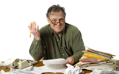 Older man looking confused with paperwork and an adding machine
