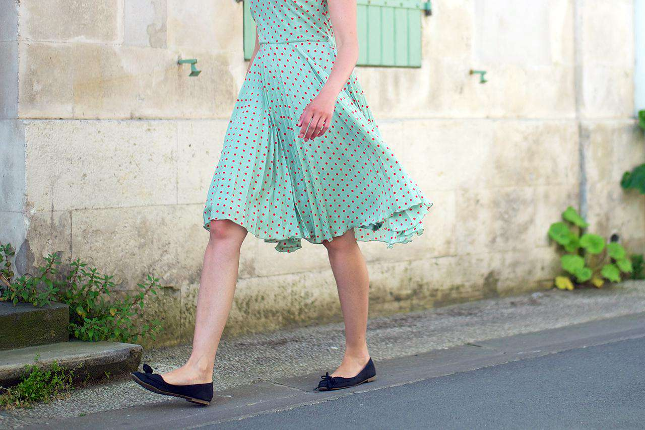 Woman in a green dress walking outside on a paved pathway