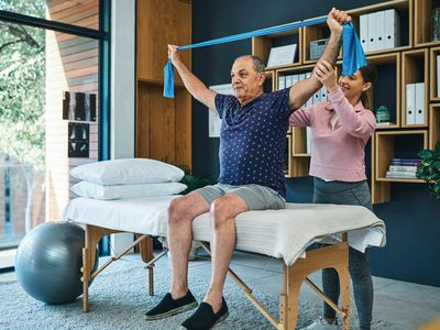 Physical therapist assists person with arthritis do therapeutic exercise