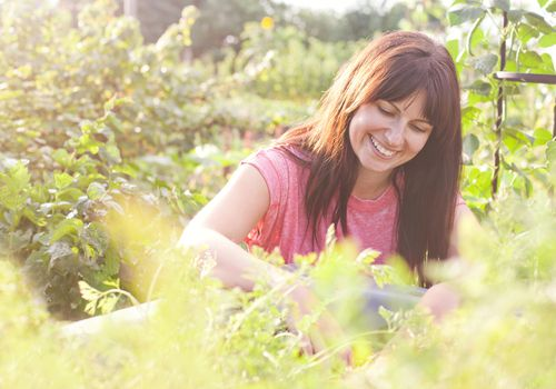 woman smiling while gardening