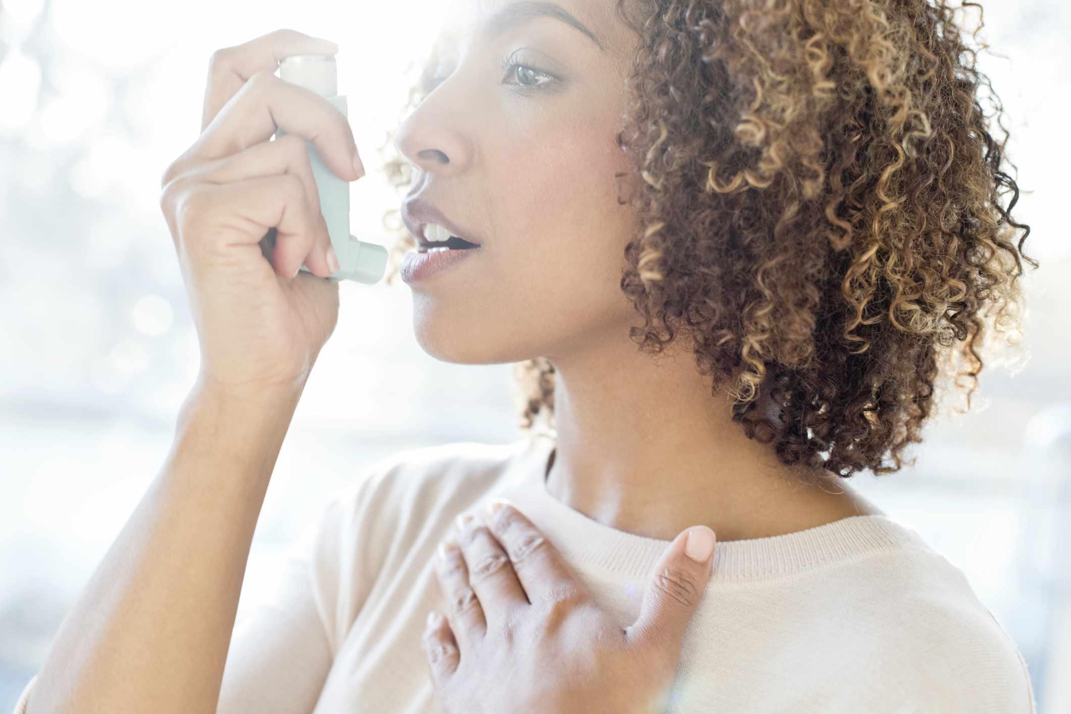 Mid adult woman using inhaler - stock photo Mid adult woman using inhaler.
