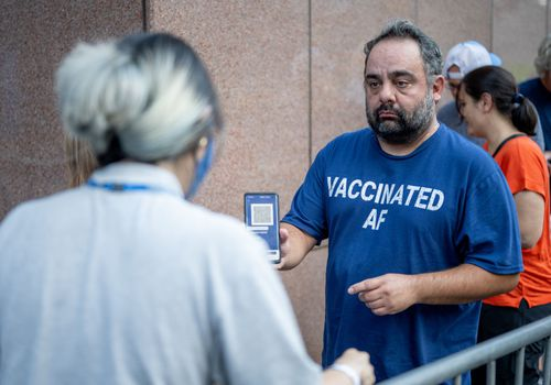 A person presents his proof of vaccination while standing in line for the Foo Fighters show as Madison Square Garden reopens