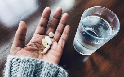 Woman holding vitamins in her hand.