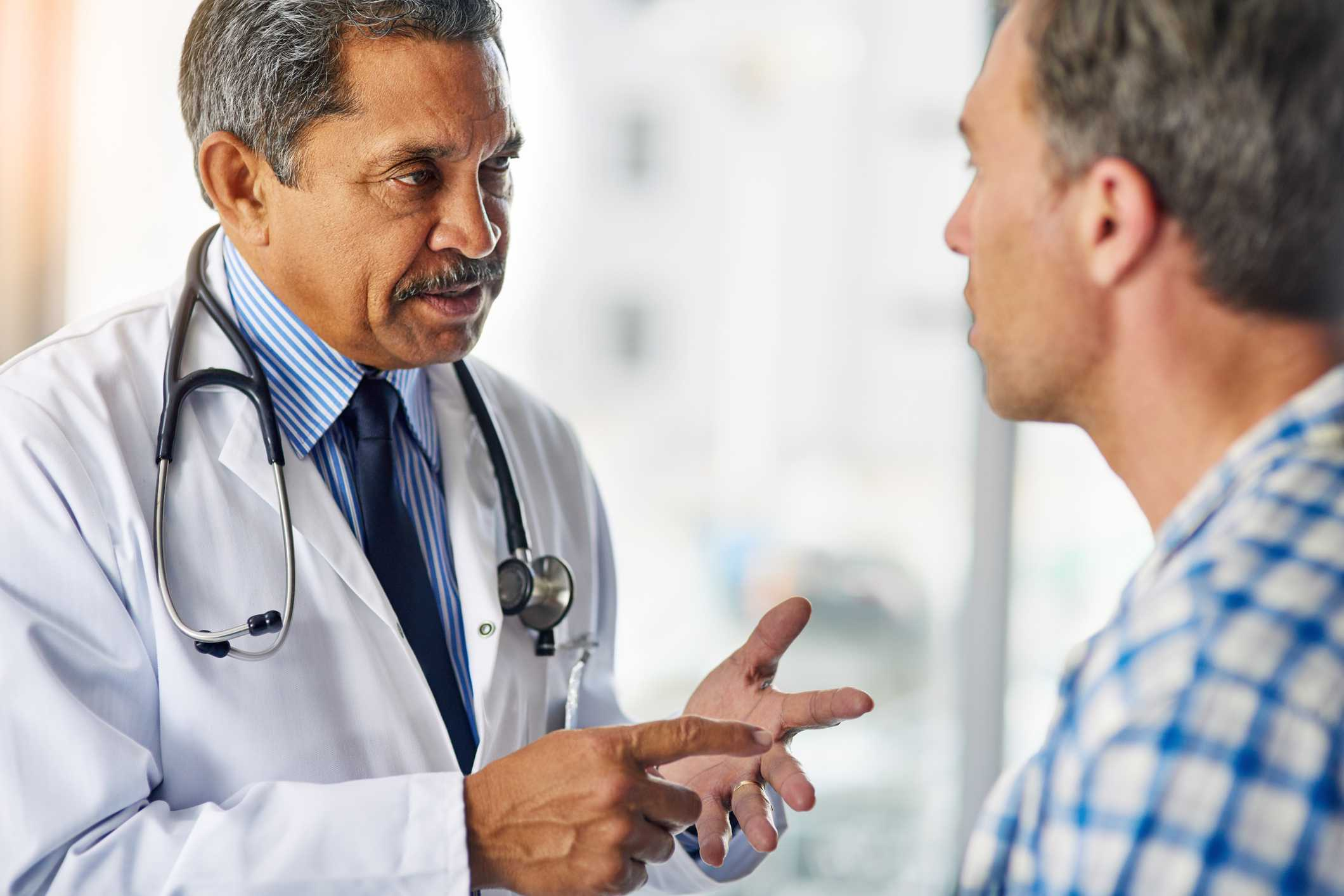 Male doctor speaking to male patient