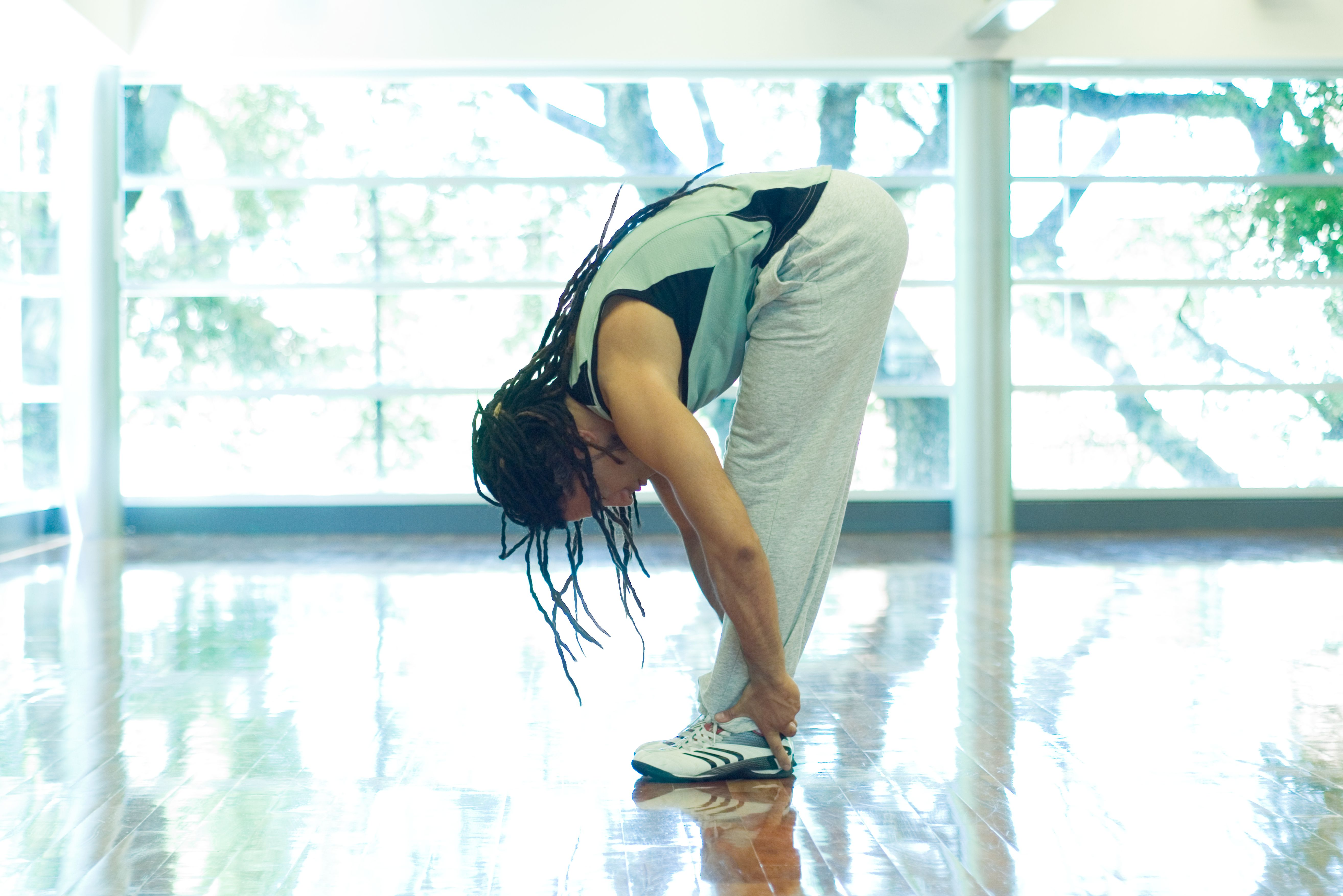 Man doing standing forward bend, full length, side view
