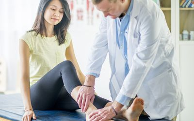 Woman having her ankle examined