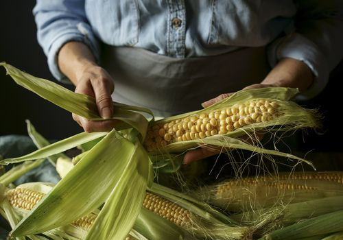 a person shucking corn