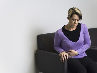woman with stomach pain sitting in doctor's office waiting room