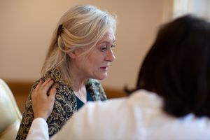 Gray-haired woman appears confused and doctor has hand on her shoulder