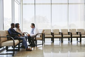 Doctor discussing with family while sitting hospital waiting room - stock photo