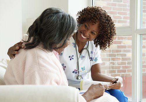a nurse sitting with a senior patient